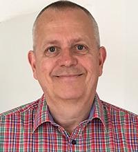 Närbild på Martin Persson, förvaltningschef i Lomma kommun. Martin Persson har rödrutig skjorta och ler.