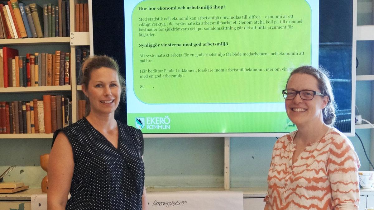 Caroline Glanz, fd huvudskyddsombud i Ekerö kommun, och Miia Borg, Hr-konsult i Ekerö kommun, står framför en storbildsskärm där Suntarbetslivs arbetsmiljöutbildning syns.