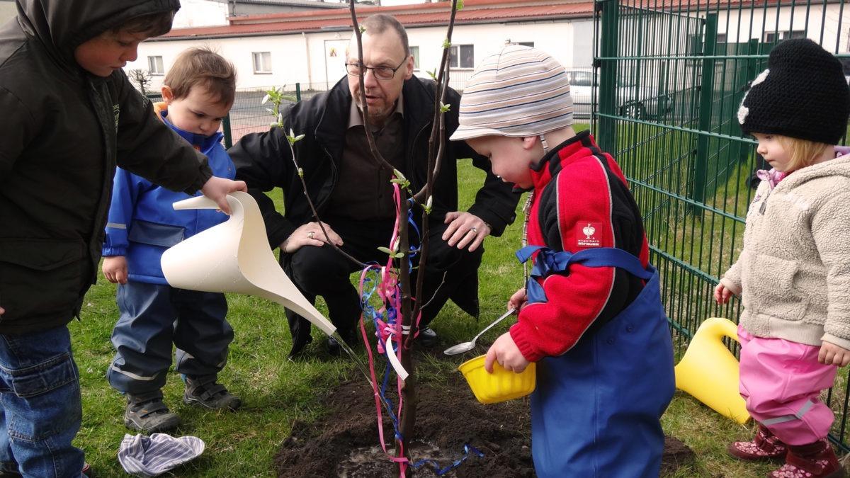Tre små barn i galonkläder hjälps åt att vattna en planta. i ringen med barnen sitter en vuxen äldre man på huk.
