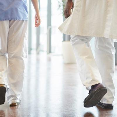 Fallolyckor. Två personer i sjukhuskläder syns bakifrån gå i en ljus sjukhuskorridor med blankt golv.