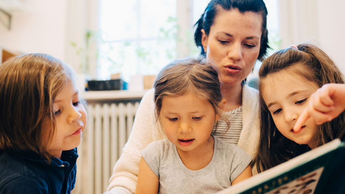 förskollärare läser bok för tre små flickor. I bakgrunden syns ett fönster och en hylla.