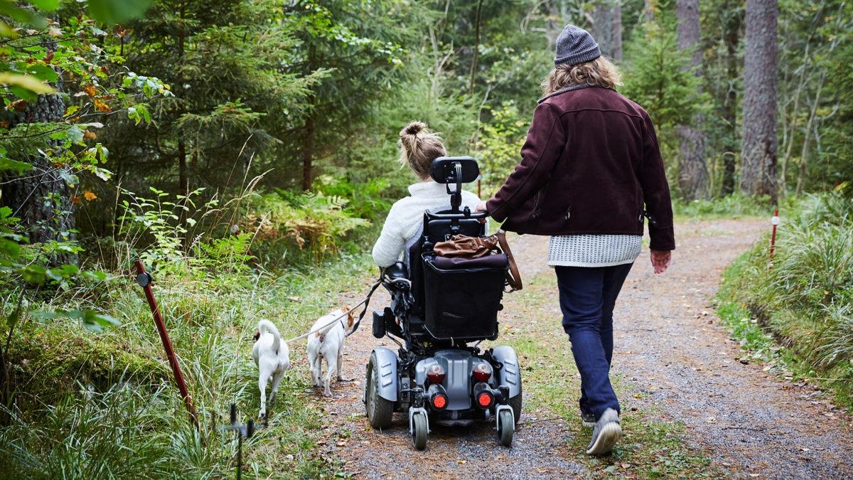 blond kvinna i rullstol och brunhårig gående man syns bakifrån gåendes på en skogsväg med mycket grönt runt omkring.