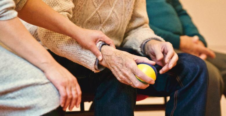 två personer sitter intill varandra, den ene iklädd en civil tröja, med en stressboll i handen. den andre i tröja och med handen på den förstes arm.