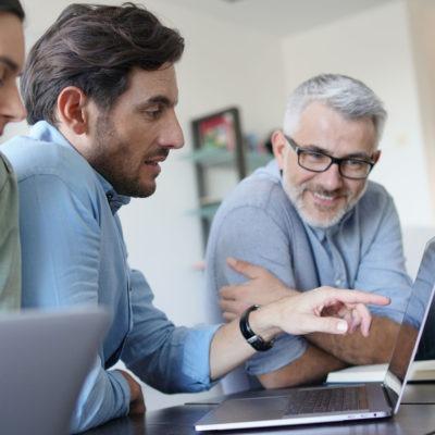 Tre kollegor med laptops vid bord.