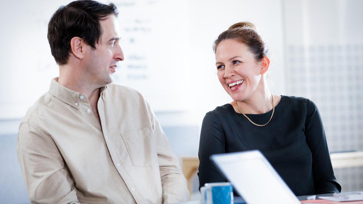 en man och en kvinna ser på varandra sittandes vid ett bord. Kvinnan ler.