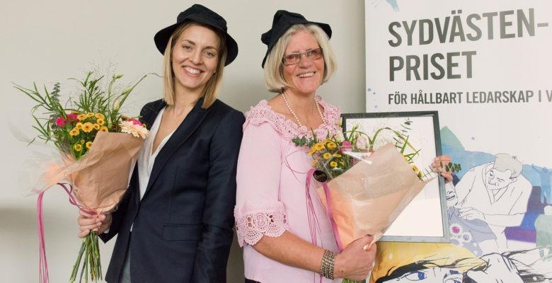 Anna Thuresson och Annette Eriksson, chefer i Borås respektive Marks kommun. Två glada kvinnor i svarta hattar, rygg mot rygg , med varsin blombukett.