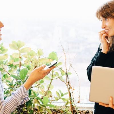 Två glada kvinnor vid ett fönster i kontorsmiljö, en med dator, en med mobil, som pratar med varandra.