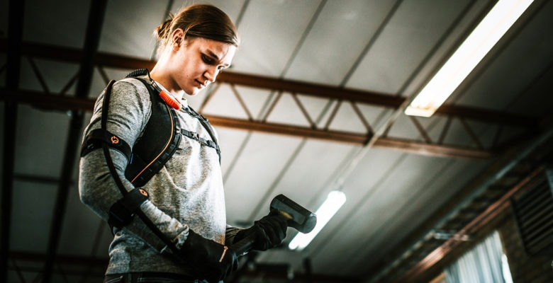 ung kvinna iklädd grå tröja och med en staällning på kroppen, liknande en ryggsäck. Ställningen är ett så kallat exoskelett.