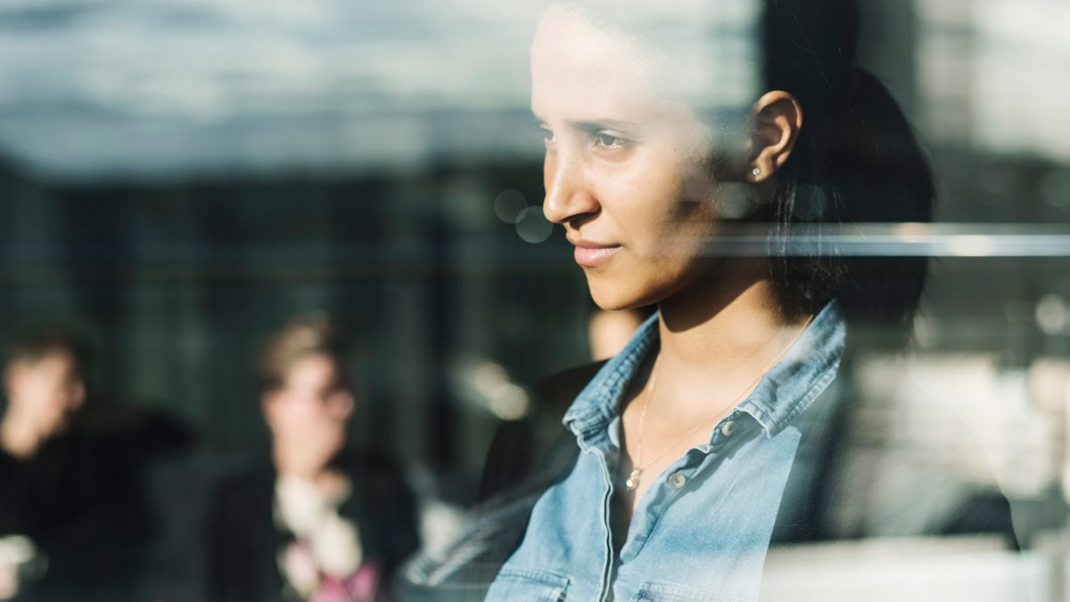 kvinna i blå jeansskjorta och uppsatt hår ser ut genom fönster med sol utanför.
