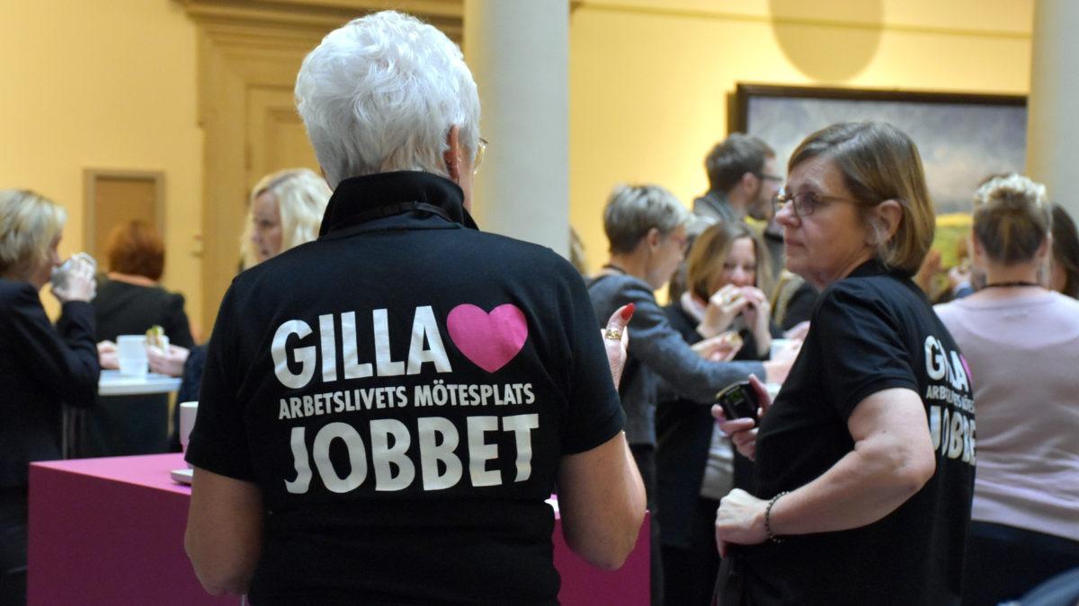 en grupp människor med ryggen mot betraktaren, har på sig svarta tröjor med rosa GillaJobbet-logga på ryggen.
