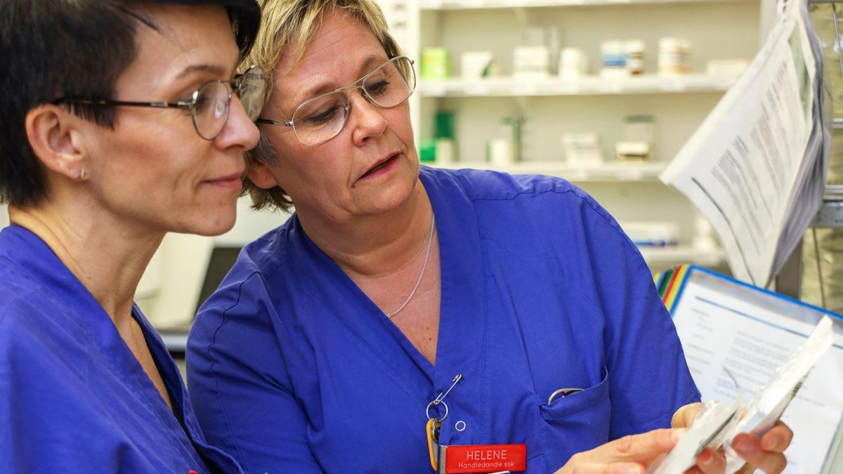 handledning på medicinavdelning 6 på Skaraborgs sjukhus i Lidköping. Två kvinnor i sjukhuskläder, den ena visar den andre ett paket med dropp.