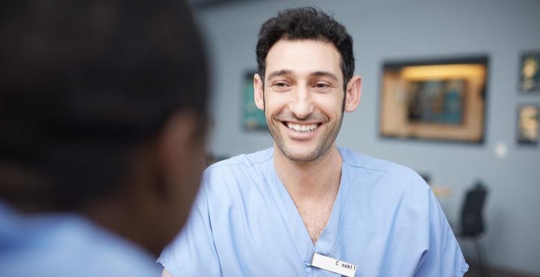 Närbild av leende ung man i vårdkläder