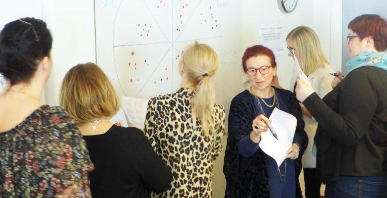 En grupp personer står med ryggen mot ett papper och väntar på att få fylla i papperet. En kvinna i mitten har just vänt sig om med ansiktet mot kameran, med en penna i handen.