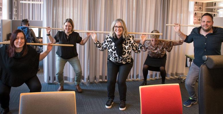Fem personer på kontorsarbetsplats gör pinngympa för rörelse på arbetstid.