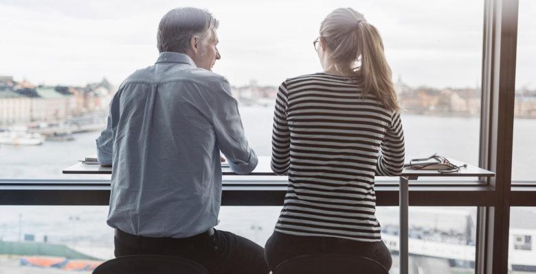 en man och en kvinna sitter med ryggen mot kameran bredvid varandra på höga pallar, och ser ut genom ett fönster.