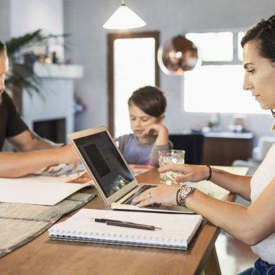 Kvinna jobbar hemma med bärbar dator och familj i bakgrunden