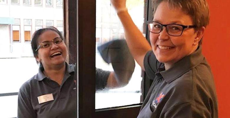 Anna Cederqvist, kommundirektör i Vara, putsar fönster tillsammans med en glad medarbetare.