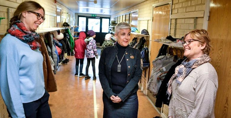 Pedagogerna Kristina Skogberg och Madeleine Holtz pratar me rektorn Anna Pilebro bryngelsson i en korridor. Några barn i bakgrunden.
