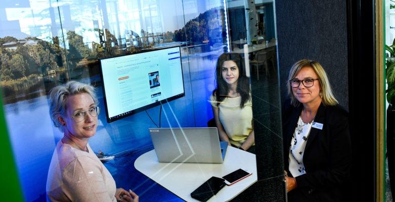 Bild på Malin Jacobsson, Yasemin Esen och Ghita Flinckman som sitter runt ett bord med en dator. Rummet har glasväggar och ser futuristiskt ut.