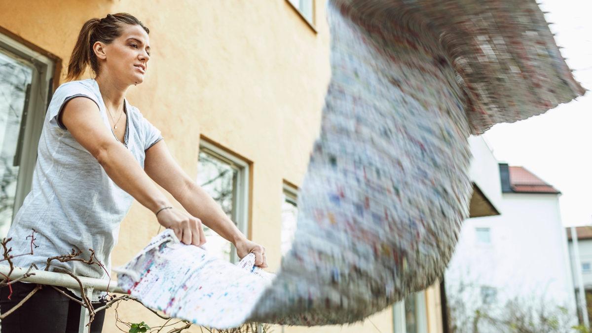ung kvinna på balkong skakar en grå matta.