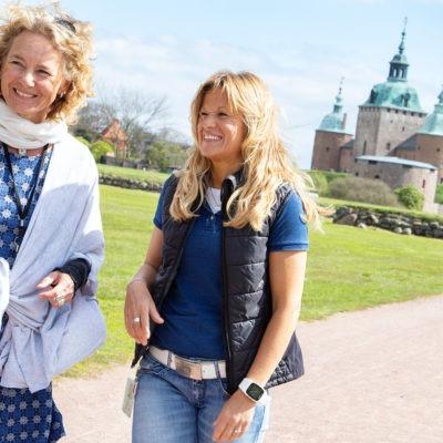 Maria Simonsson och Stina Winblad, företagshälsovården i Region Kalmar, går på en väg i öppet soligt landskap med Kalmar slott i bakgrunden.