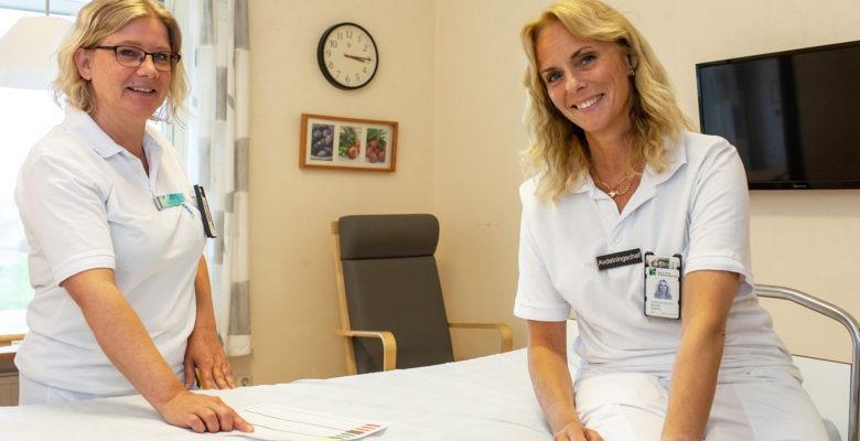 Marie Olsson, undersköterska och skyddsombud, och Maria Grans, avdelningschef, Ljungby lasarett. de båda står vid en sjukhussäng i arbetskläder och tittar mot kameran.