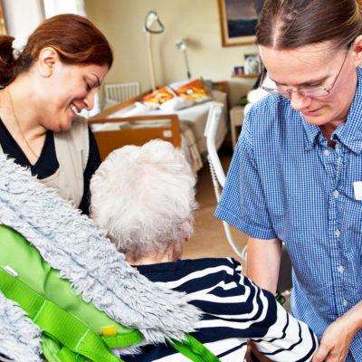 två undersköterskor i arbetskläder hjälper en gammal kvinna att sätta sig i sin stol, i hemmiljö.