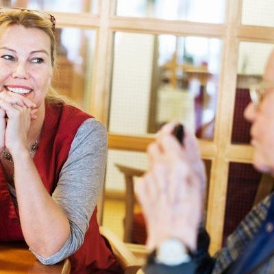 Leende kvinnlig undersköterska i röd arbetsväst sitter vid ett bord med en äldre man.