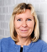 Kuratorn Birgitta Härfast mot vit tegelvägg.