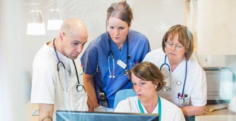 Sjukvårdspersonal som trängs framför datorskärm