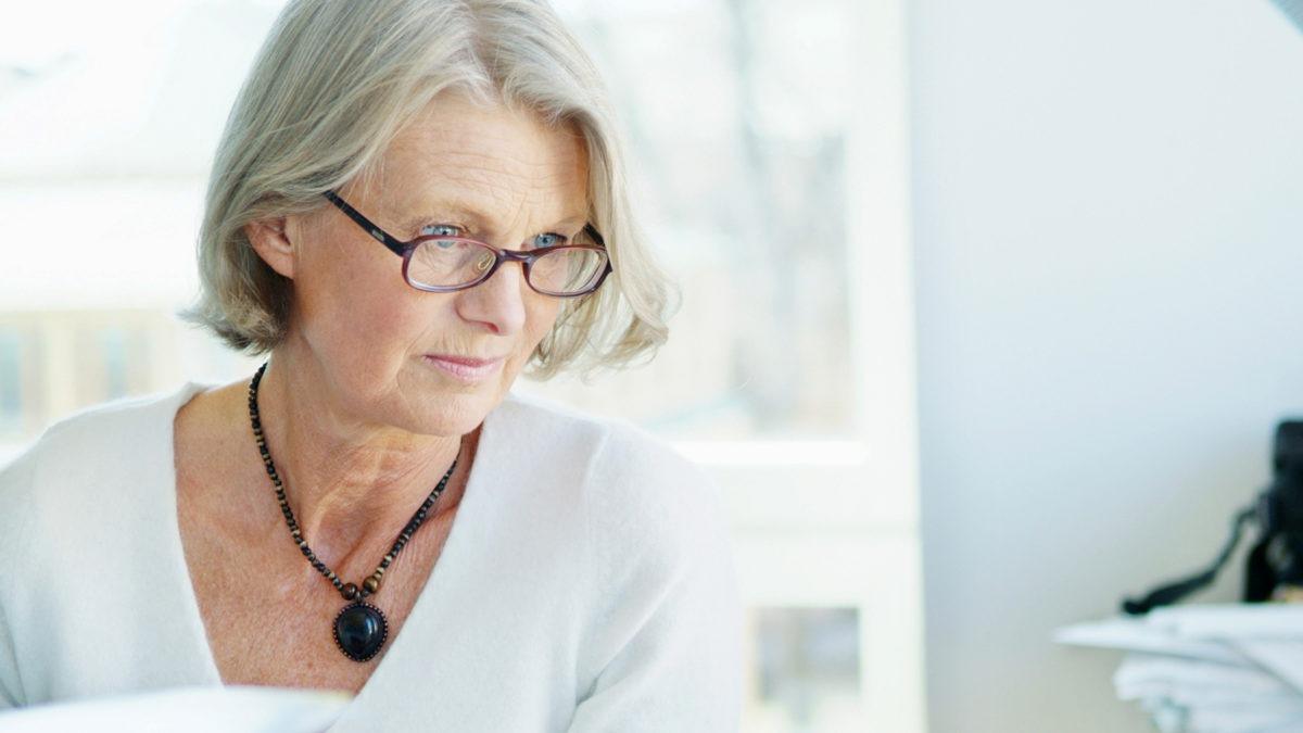 äldre kvinna i vit tröja och ljusgrått hår, i kontorsmiljö