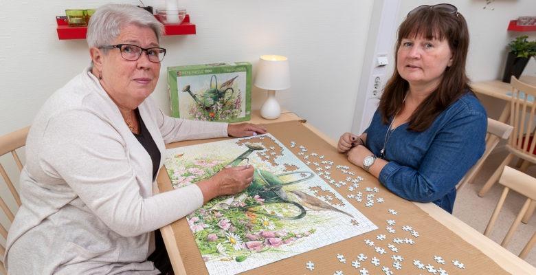 Barbro Antonsson och Anette Wollin på 1177 vårdguiden i skövde sitter vid ett bord och lägger pussel.