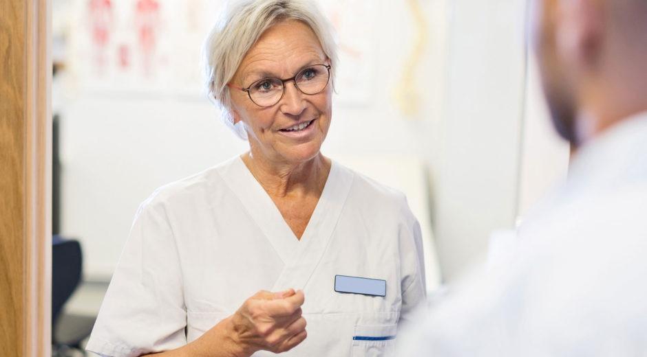 Foto på äldre läkare (kvinna) som pratar med någon.