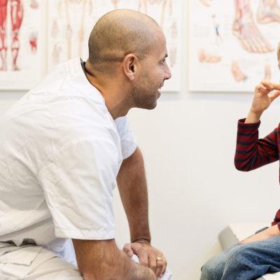 läkare sitter i ett undersökningsrum framför en pojke som sitter på en brits. De pratar med varandra.