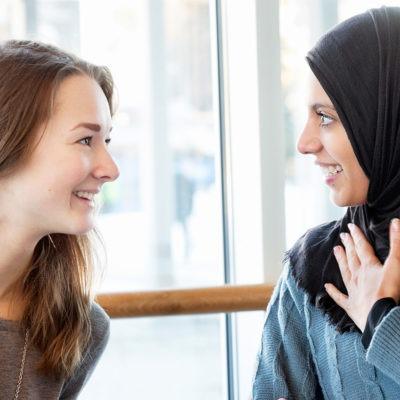 Två kvinnor som pratar med varandra.