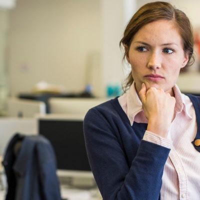 Fundersam kvinna i kontorslandskap