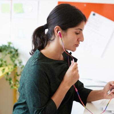 Kvinna på kontor pratar i mobil och tittar på dator.