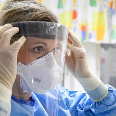 Sjukvårdspersonal med skyddskläder och ett ansiktsvisir.