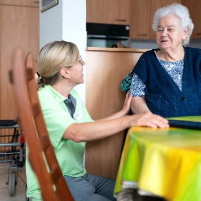 Hemtjänstpersonal i samtal med äldre dam.