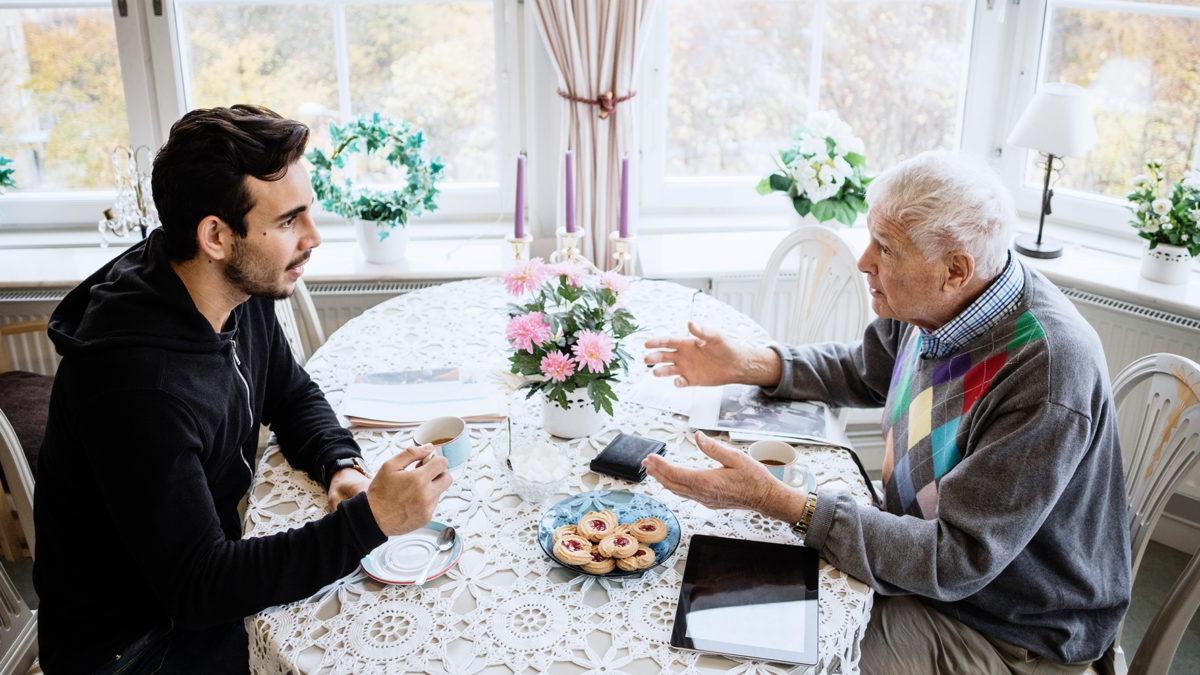 En ung man och en äldre man sitter vid ett bord och pratar.