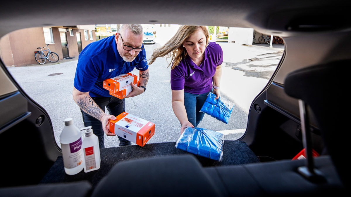 Krister Wessman och Jessica Karlsson lastar in handsprit mm i en bil.