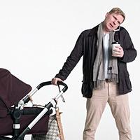 Man med barnvagn i ena handen och mobiltelefon klämd vid örat.