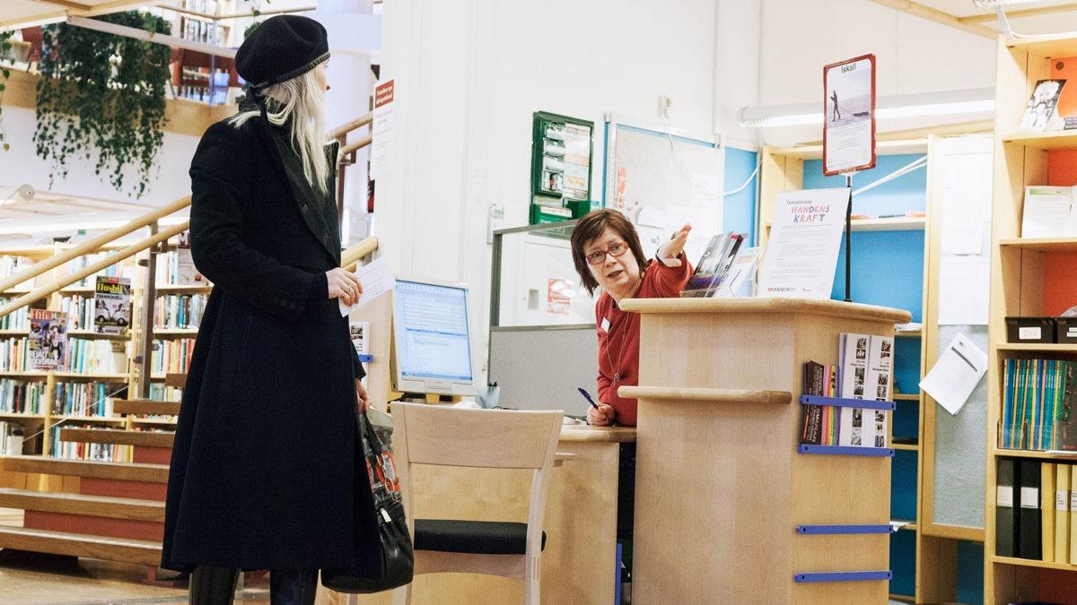 Besökare och personal vid infodisk på bibliotek.