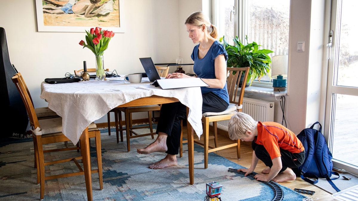 Kvinna som arbetar framför dator vid matsalsbord hemma. BArm leker med tågbana under bordet.