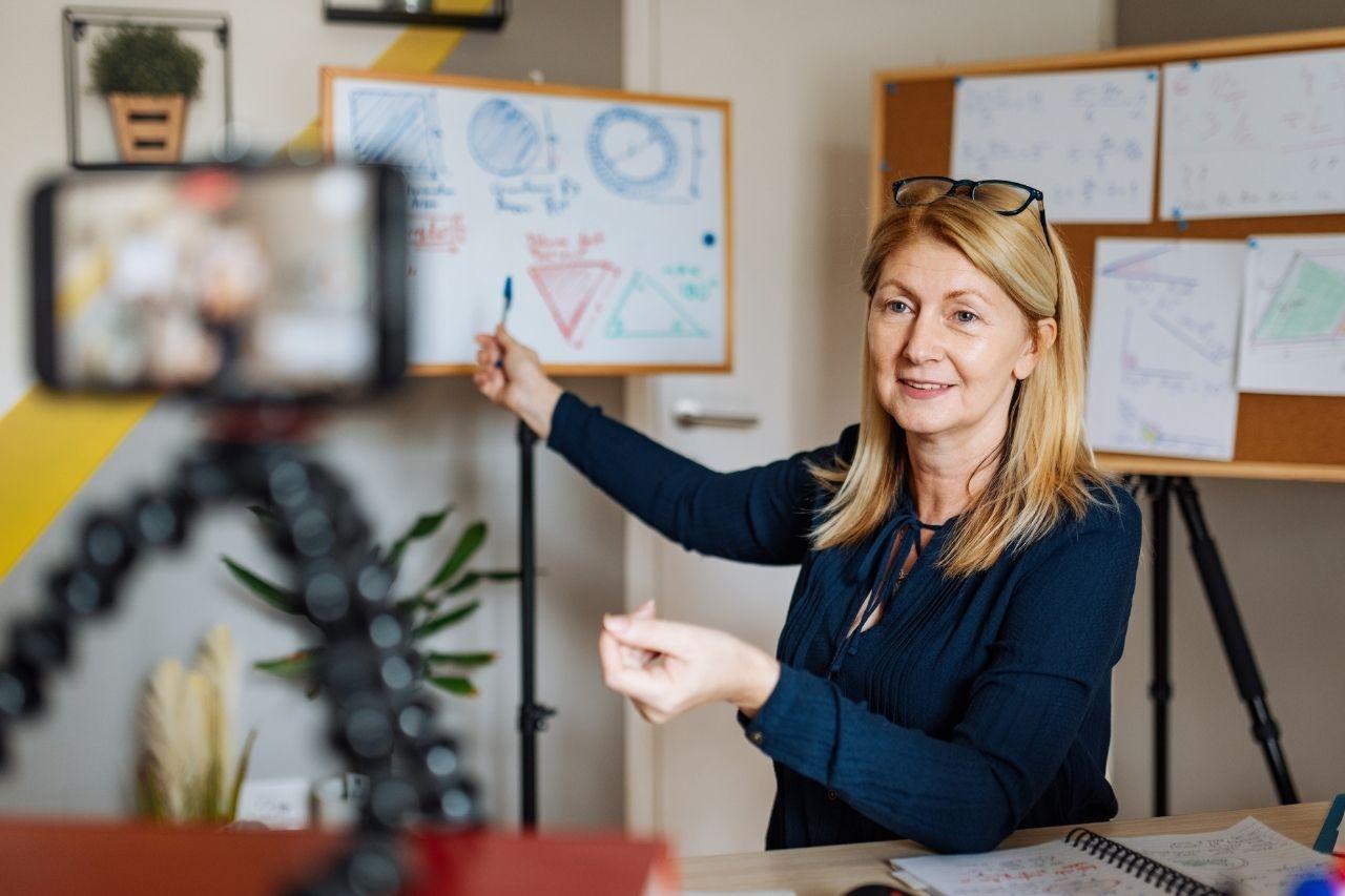 Kvinna som visar modeller på en tavla inför en videokamera