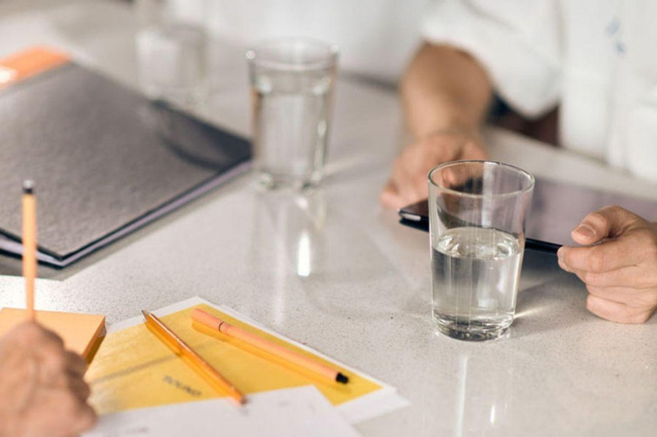 Händer på ett bord vid möte om arbetsmiljö