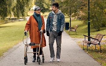 Äldre kvinna med rollator går med ung man i park.