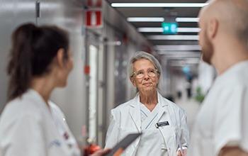 Äldre vårdpersonal pratar med kollegor i sjukhuskorridor.