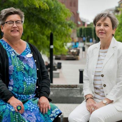 Kristina Rauer och Marie Söderqvist sitter på en bänk utomhus.