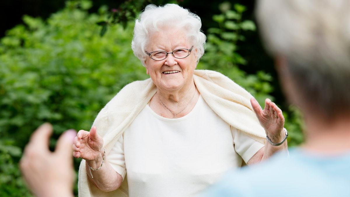 Äldre dam möter person med öppna armar och social distans.